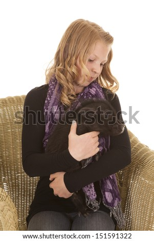 A young girl holding a little pig in her arms with a small smile on her lips. - stock photo