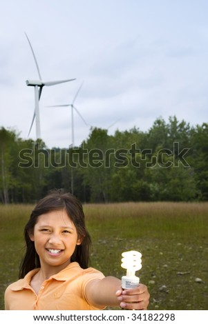 A young girl holding an illuminated CFL bulb in front of a wind farm. - stock photo