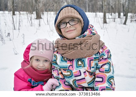 A young girl holding the hand of her older sister, winter landscape in the blurred background - stock photo