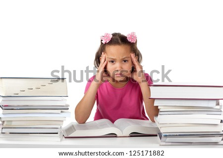 A young girl holds her head in a frown at a desk covered with many big books. - stock photo