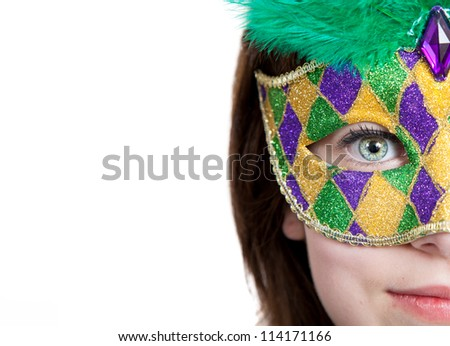 A young girl in a gold, purple and green mardi gras mask with copy space - stock photo
