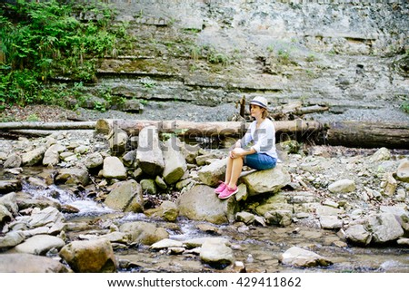 A young girl in a hat sits on the river and thinking of something beautiful