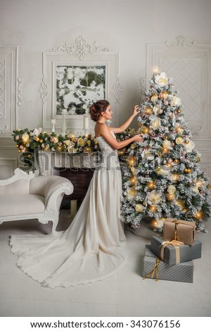 A young girl in a white dress decorates Christmas tree in the living room - stock photo