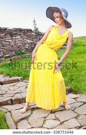 A young girl in a yellow dress in the park - stock photo