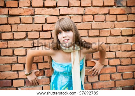 A young girl in dress by the wall - stock photo