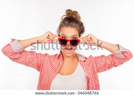A young girl in glasses with angry expression of her face - stock photo