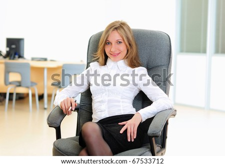 A young girl in his office sits in a gray chair.