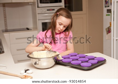 A young girl is baking cupcakes in their kitchen at home in er - stock photo