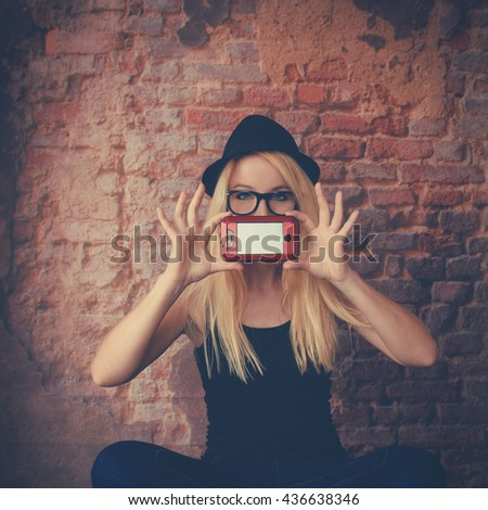 A young girl is holding a blank cell phone to her face against a hip brick background for a communication or message concept - stock photo