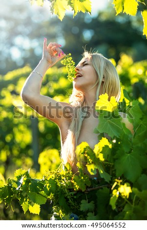 A young girl is holding grapes and enjoying