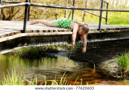 A young girl is leaning over a small bridge playing in the creek with a stick.