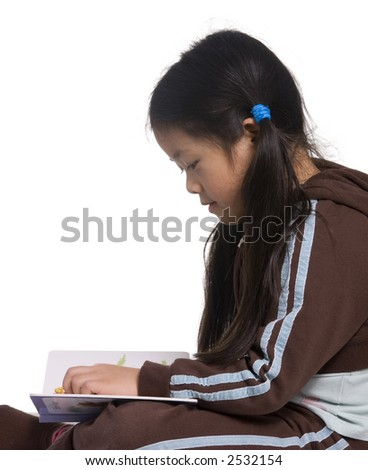 A young girl is lost in imagination as she reads a book - stock photo