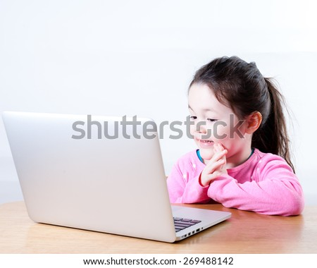 A young girl is pleased about something on a computer.