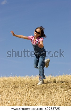 A young girl is prancing around in an already harvested wheat field.