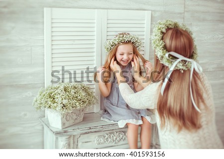 A young girl is sitting on the fireplace. Her mother is tiding her hair. They are both having floral wreathes and casual clothes on. The atmosphere of happiness is all around them. - stock photo