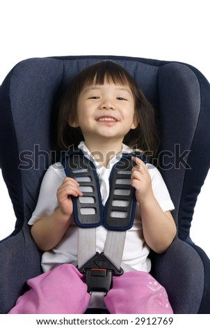 A young girl is strapped into a car seat for safety. - stock photo