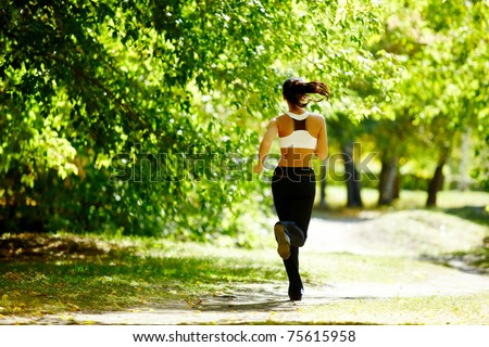 A young girl jogging in the park - stock photo
