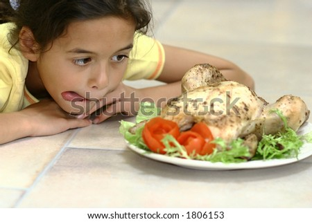 A young girl licking her lips as she gets tempted by the delicious whole roast chicken