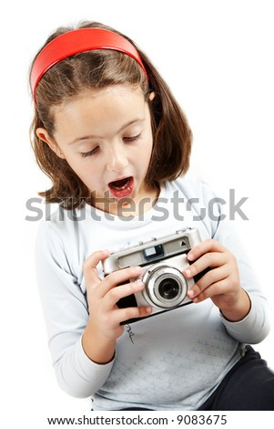 A young girl looking surprised an old camera. Isolation on white.