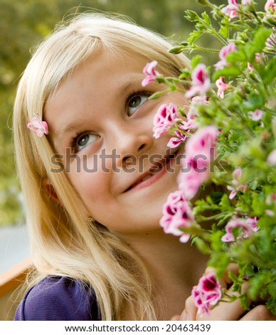 A young girl loving flowers - stock photo