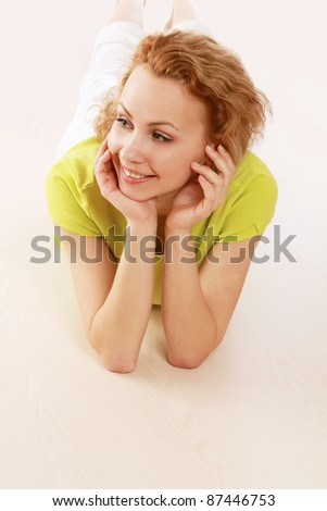 A young girl lying on the floor, isolated on white - stock photo