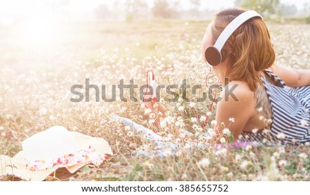 A young girl lying on the grass listening to music, relax on soft and blurred background - stock photo