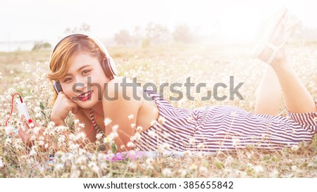 A young girl lying on the grass listening to music, relax on soft and blurred background
