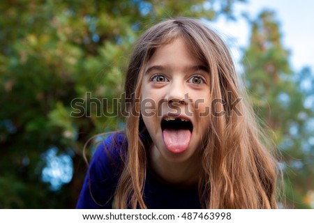 young girl makes funny face camera stock photo (edit now)- shutterstock