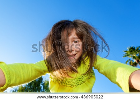 A young girl playing at a playground, climbs up and over the camera as she looks into the lens nervously. - stock photo