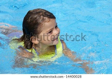 a young girl playing in pool - stock photo