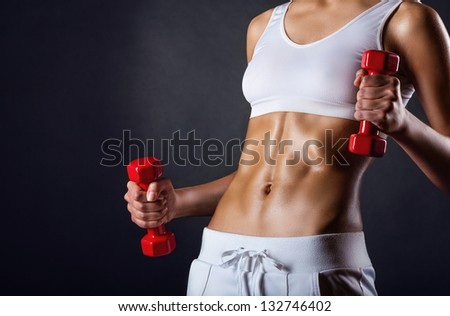 A young girl playing sports with weights on a dark background - stock photo