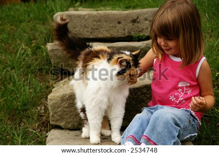 A young girl playing with a kitty - stock photo
