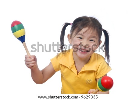 A young girl playing with maracas. Childhood. - stock photo