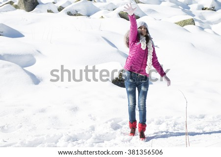 A young girl plays with snow in winter in the mountains - stock photo