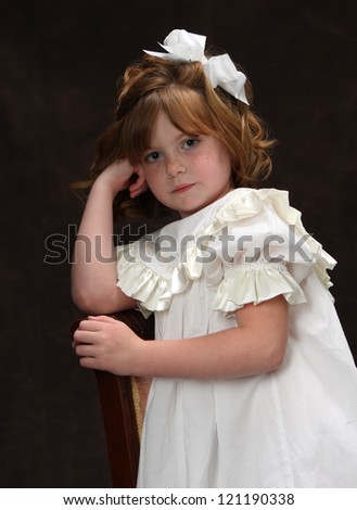 A young girl poses in an antique dress in a classic pose and expression