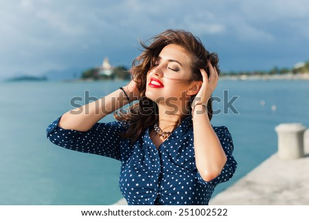a young girl poses with red lips on the street - stock photo