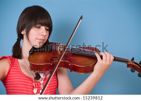 A young girl practicing on her viola. - stock photo