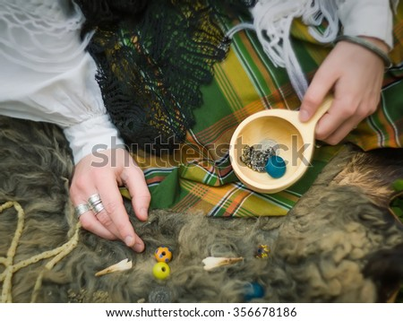 A young girl prepares some things for witchcraft - stock photo
