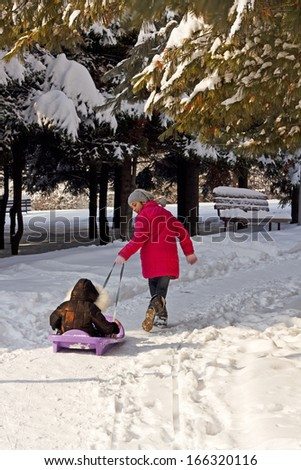 A young girl pulling her sister to sled in winter time  - stock photo