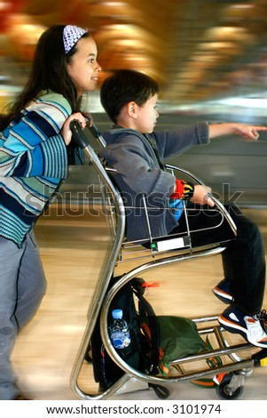 A young girl pushing her brother on the baggage trolley towards the departure lounge at an airport, with lots of movement. - stock photo