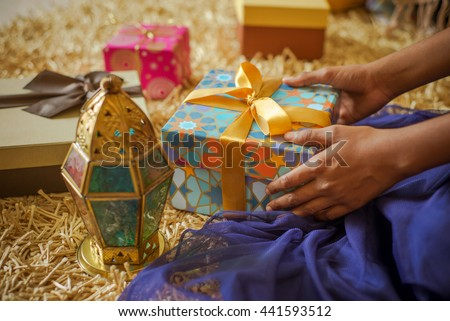 A young  girl receiving a gift. Eid celebration -a happiest moment for a kids. Stock photo. - stock photo