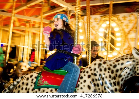 A young girl rides a carousel in winter.  She has on a hat, warm coat, and gloves.  She is frozen in action but all around her is a blur from the carousel turning. - stock photo