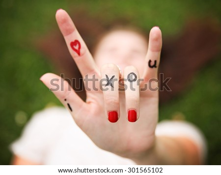 a young girl's hand with lettering i heart x o u written on it during summer making the rock on sign - stock photo