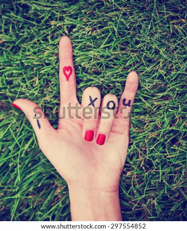 a young girl's hand with lettering i heart x o u written on it in the grass during summer making the rock on sign toned with a retro vintage instagram filter effect app or action - stock photo