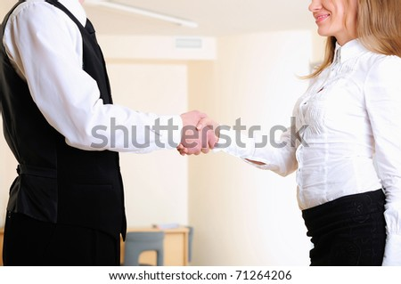 A young girl shakes hands with his colleague in the office.