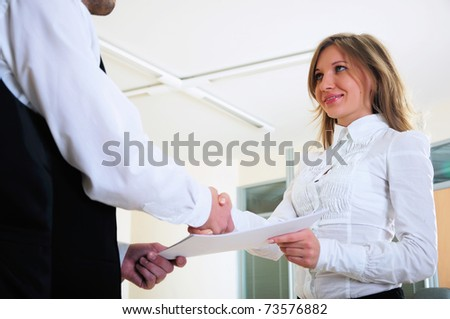 A young girl shakes hands with his colleague in the office. - stock photo