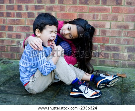 A young girl showing compassion to her little brother after he trips over and hurt his leg. - stock photo