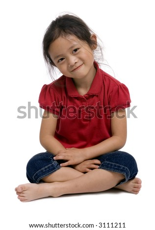 A young girl sits cross legged on the floor. - stock photo