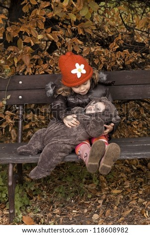 A young girl sits with her baby brother on a park bench during the Autumn season. - stock photo