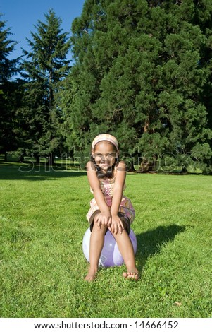 A young girl, sitting on a ball, in a field of grass in a park, smiles big. - vertically framed - stock photo